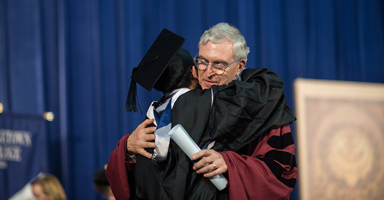 Dean Chester Gillis embraces a student at the 2016 Georgetown College Commencement ceremony.