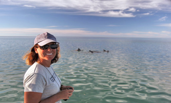 Prof. Janet Mann poses with dolphins in a bay in the background
